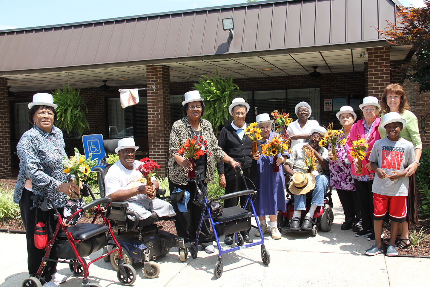 Silver Saints hold flower arrangements they made and then delivered to nursing home residents. The Saints program encourages residents to use their talents to give back to their community.